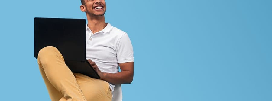 Cheerful black student with laptop looking away